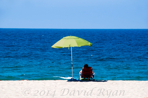 Woman sitting under umbrella on beach