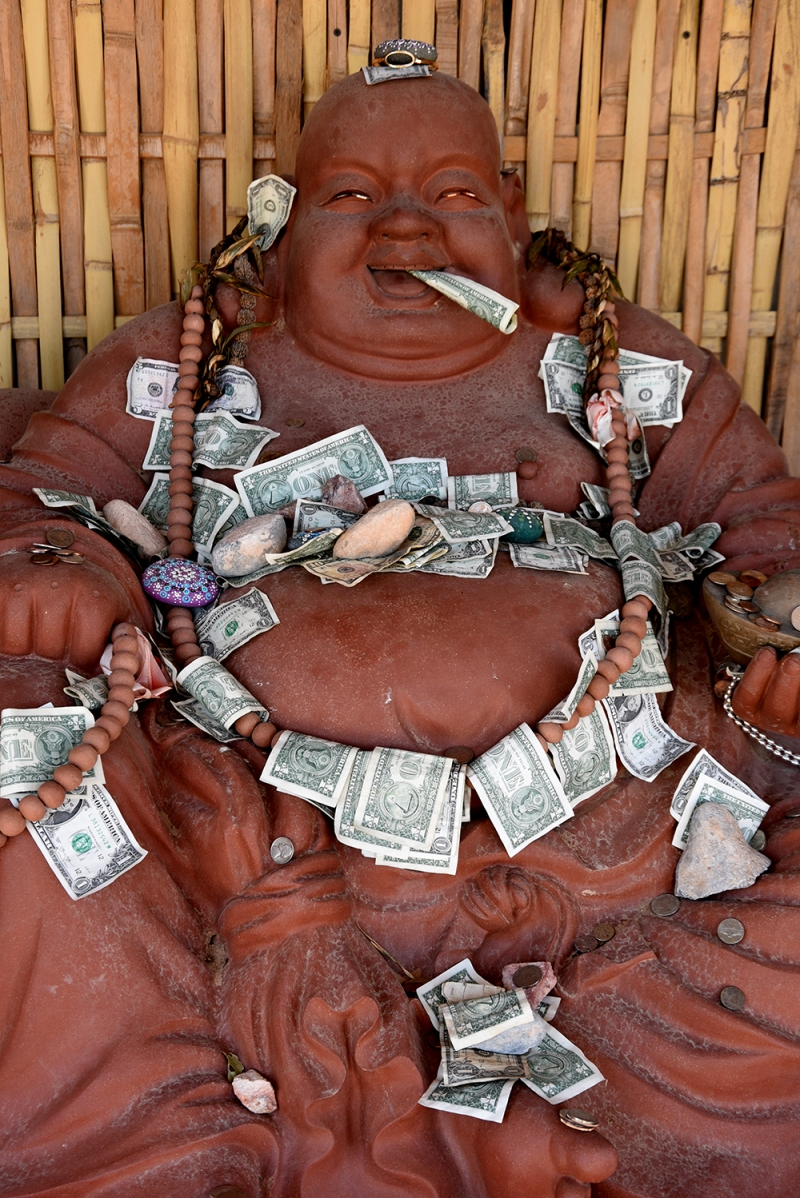 A laughing Buddha covered with cash